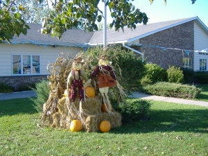 A scare crow display on hay bails and pumpkins