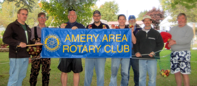A group of men holding an Amery Area Rotary Club banner